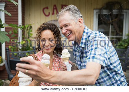 Couple with ice cream taking selfie outside cafe - Stock Photo