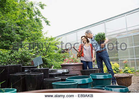 Couple shopping for planters in plant nursery greenhouse - Stock Photo