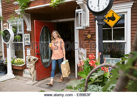 Woman with coffee and shopping bag leaving market - Stock Photo
