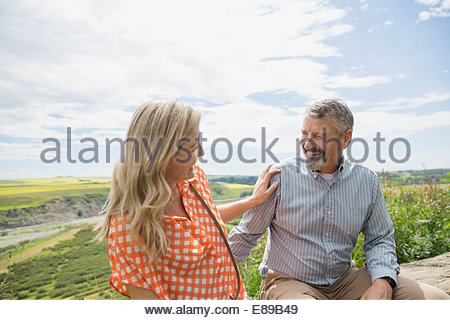 Couple laughing outdoors with countryside in background - Stock Photo