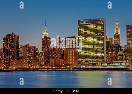 New York City Landmarks - Midtown Manhattan New York City skyline view of the Empire State Building, The United Nations and the iconic Chrysler Building. Photographed during the blue hour of twilight. Stock Photo