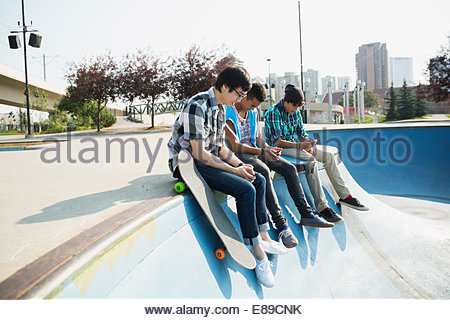 Teenage boys sitting at edge of skateboard ramp - Stock Photo