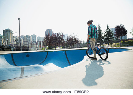 Teenage boy on bicycle at skateboard park - Stock Photo