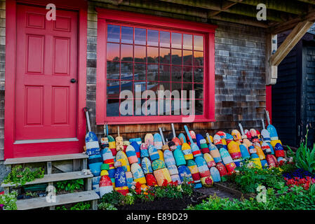 Rows of colorful buoys lined up in a storefront with Motif Number One reflected in the window panes. Bradley Wharf - Stock Photo