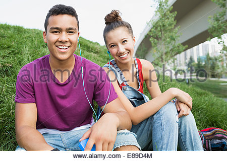 Portrait of smiling teenage couple in grass - Stock Photo