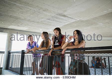 Teenagers leaning on railing - Stock Photo