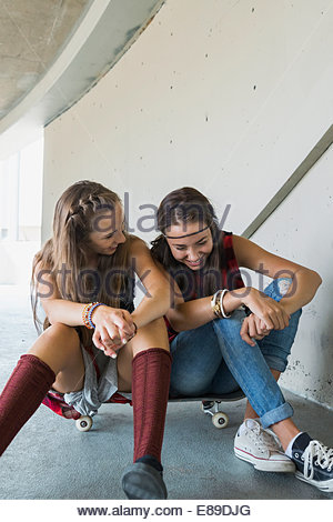 Teenage girls laughing on skateboard - Stock Photo