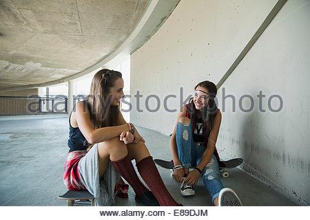Teenage girls talking on skateboards - Stock Photo