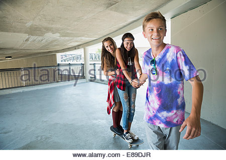 Teenage boy pulling teenage girls on skateboard - Stock Photo