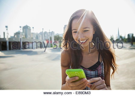 Smiling teenage girl with cell phone - Stock Photo