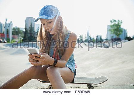 Teenage girl sitting on skateboard at sunny park - Stock Photo