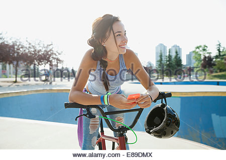 Teenage girl with cell phone on bicycle - Stock Photo
