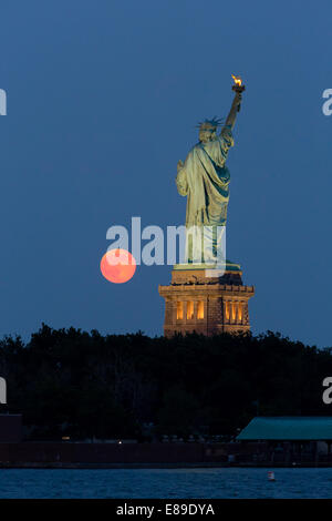 The super moon rises next to the Statue of Liberty during twilight. - Stock Photo