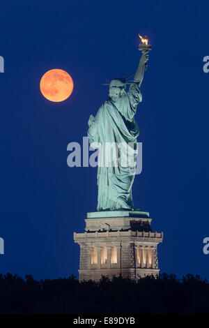 The super moon rises next to the Statue of Liberty during the blue hour. - Stock Photo
