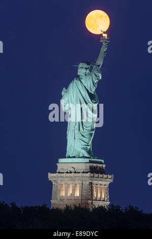The super moon rises over the Statue of Liberty during the blue hour. - Stock Photo