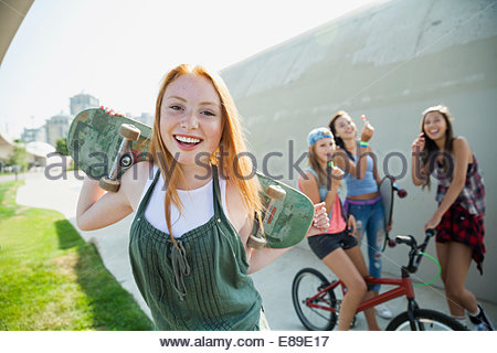 Portrait of smiling teenage girl with skateboard - Stock Photo