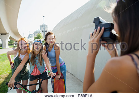 Teenage girl photographing friends with instant camera - Stock Photo