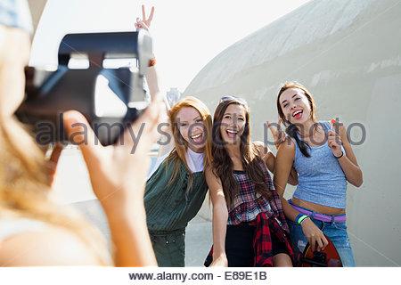 Teenage girl photographing friends - Stock Photo