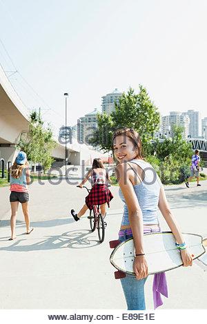 Portrait of teenage girl with skateboard - Stock Photo