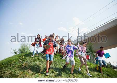 Teenagers walking down grassy slope - Stock Photo