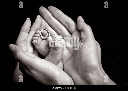 An art black & white image of the crossed feet of a newborn with wedding rings on its toes, cupped in its mothers - Stock Photo
