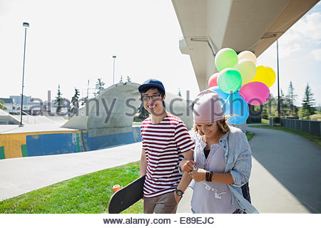 Teenage couple with balloons at skateboard park - Stock Photo