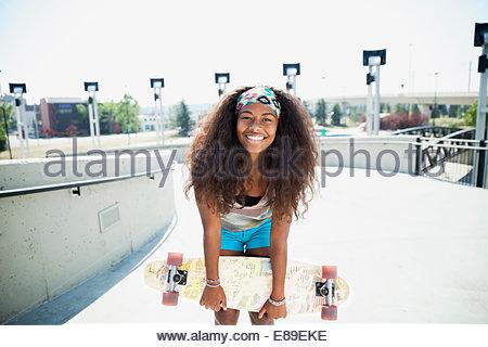 Portrait of teenage girl holding skateboard - Stock Photo