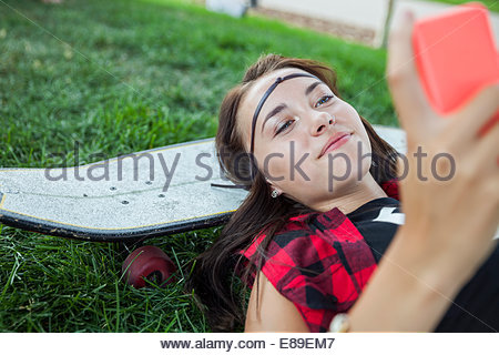 Teenage girl with cell phone laying on skateboard - Stock Photo