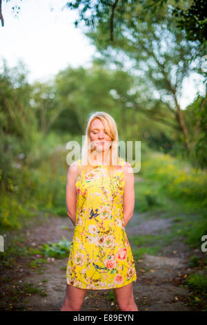 A young teenage blonde girl woman wearing yellow dress eyes closed outdoors on a warm sunny summer evening UK - Stock Photo