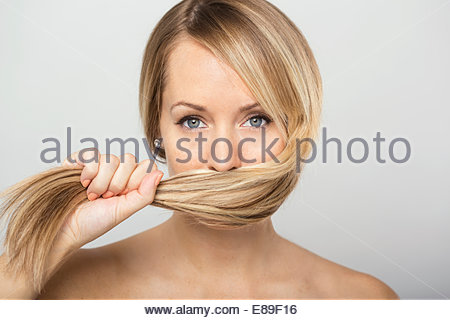 Portrait of blonde woman holding hair over face - Stock Photo