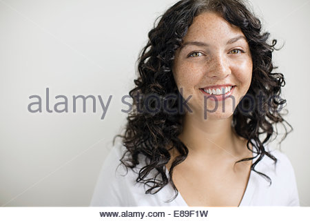 Portrait of smiling woman with curly black hair - Stock Photo