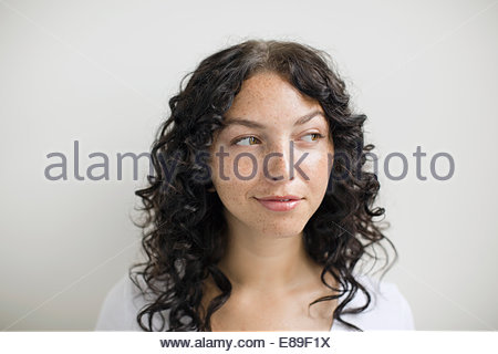 Pensive woman with freckles and curly black hair - Stock Photo