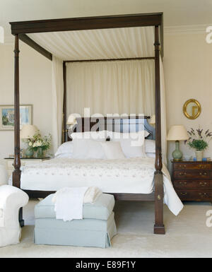 Cream drapes on dark wood four poster bed with white linen in bedroom with pale blue ottoman - Stock Photo