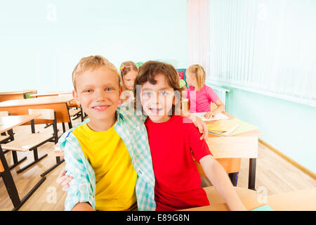 Happy boys hug and sit together in classroom - Stock Photo