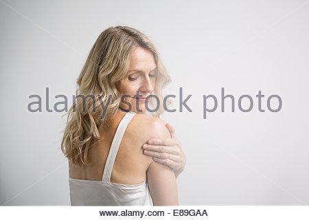 Blonde woman touching shoulder - Stock Photo