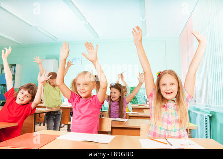 Happy kids with arms up sit in classroom rows - Stock Photo