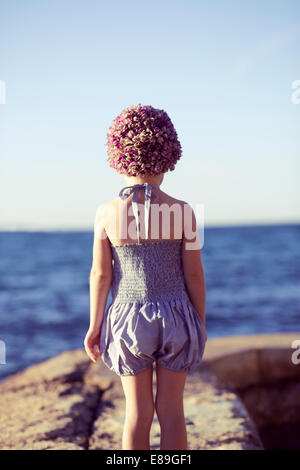 Girl in swimcap looking at the beach - Stock Photo