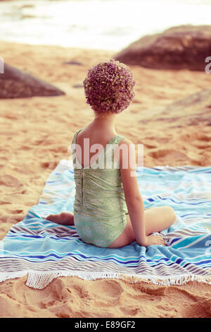 Girl in swimcap sitting on beach blanket - Stock Photo