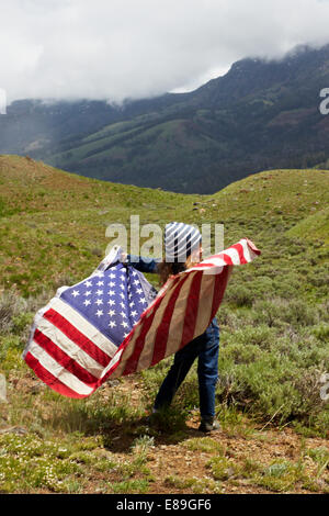 Girl with American flag in field - Stock Photo