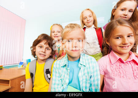 Kids sit near desk and smile in classroom - Stock Photo