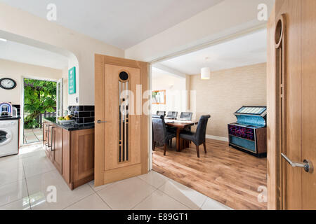 A view through double, solid wood doors from a kitchen in to a dining room in an extended & renovated home, UK - Stock Photo
