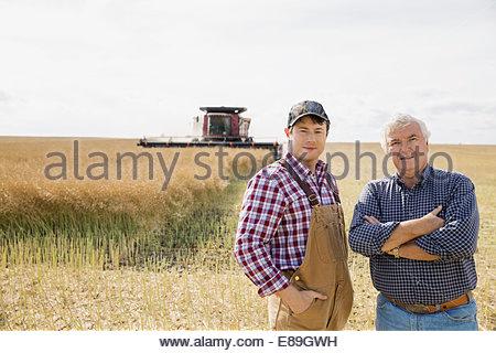 Portrait of farmers in sunny wheat field - Stock Photo