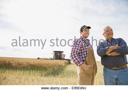 Farmers in sunny wheat field - Stock Photo