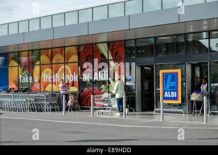 Customers & shopping carts outside German discount supermarket, Aldi in Swindon, Wiltshire, UK