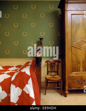Small antique chair beside large wardrobe in country bedroom with green wallpaper and red+white quilt - Stock Photo