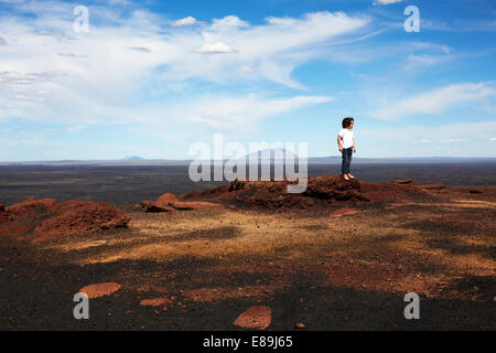 Boy Standing on rocks at Craters of The Moon - Stock Photo