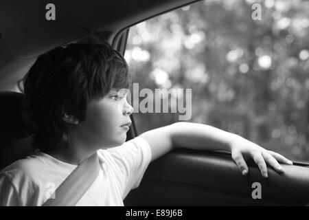 Boy lost in thought in the car, roadtrip - Stock Photo