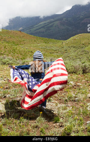 Girl wrapped in American Flag in field - Stock Photo