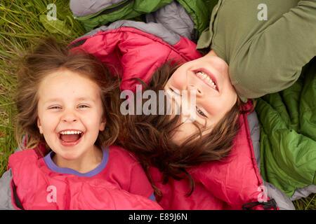 Laughing kids laying on sleeping bags