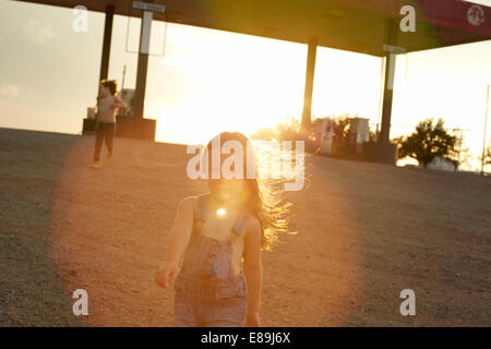 Kids at gas station at sunset - Stock Photo